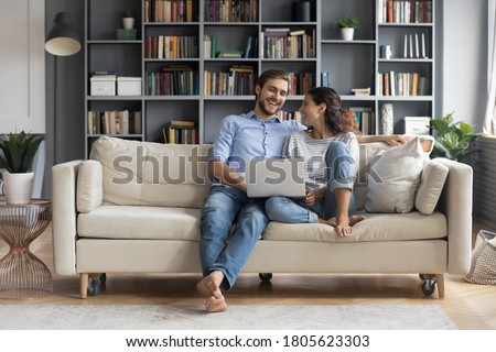Happy young relaxed couple sitting on sofa with laptop on laps, discussing funny movie, enjoying watching comedian film, shopping online or web surfing, full length front view, leisure pastime concept Royalty-Free Stock Photo #1805623303