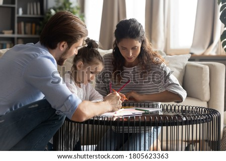 Young caring couple helping small preschool cute child daughter drawing pictures in paper album indoors. Adorable little kid girl enjoying entertaining creative activity with loving parents at home.
