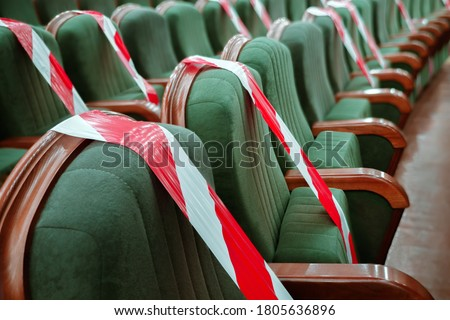 Keep your distance to avoid physical contact. Practice of social distancing. View of rows of seats marked with a warning tape in the cinema, theater, auditorium, conference hall. Protection COVID-19 Royalty-Free Stock Photo #1805636896