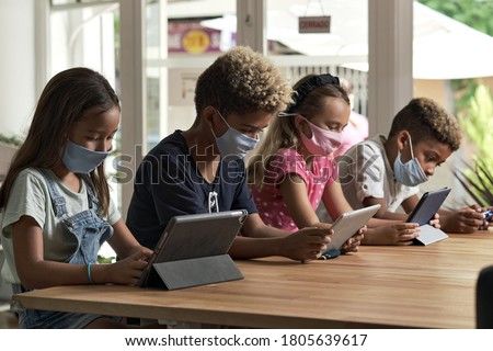 Four diverse kids wear facemasks sit at table use wireless gadgets ignoring each other prefer internet games and virtual communication. Alpha generation and modern technology overuse, phubbing concept #1805639617