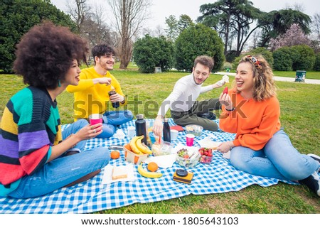 Group of multiethnic friends having pic nic - Multi racial people bonding celebrating partying on countryside - social gathering, friendship, having fun concept