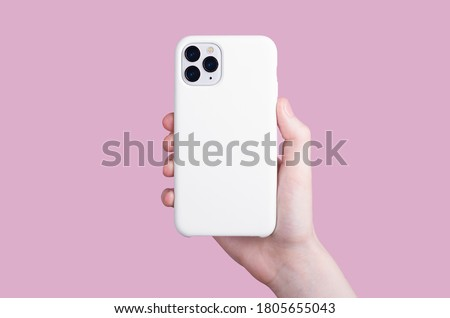 Female hand holding white iPhone 11 Pro in soft silicone white cover back view . Phone case mock up isolated on pink background