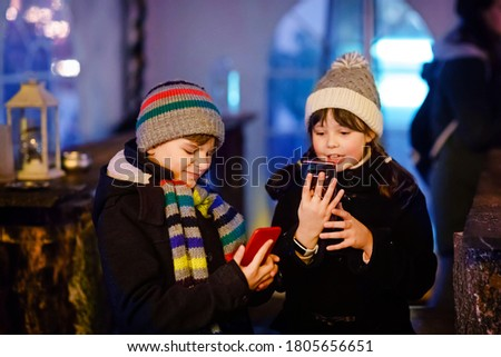 Two little kids, boy and girl having fun on traditional Christmas market during strong snowfall with taking photos with mobile smartphone or phone. Happy children, siblings and best friends