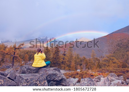 The girl photographs a rainbow on a mobile phone. Beautiful rainbow in the mountains. Travel concept. Selective focus on the girl. Royalty-Free Stock Photo #1805672728