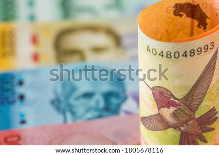Currency from Costa Rica. The highest face value of 20,000 colones rolled up against the background of other banknotes of this country Royalty-Free Stock Photo #1805678116