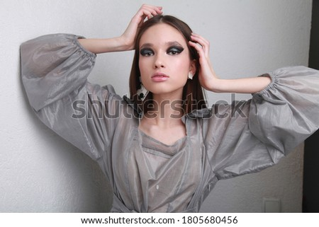 Stylish young model in silver transparent blouse and black and white handmade earrings, posing at the white wall background touching her head. Fashionable image for magazine with free space copyright