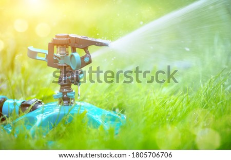 Sprinkler head watering green grass lawn. Gardening concept. Smart garden activated with full automatic sprinkler irrigation system working in a green park #1805706706