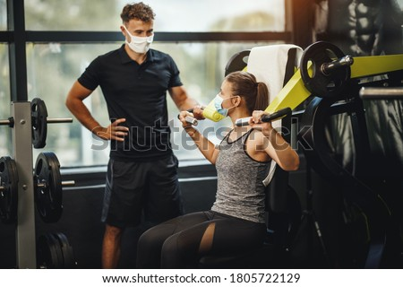 Shot of a muscular young woman with protective mask working out with personal trainer at the gym machine during Covid-19 pandemic. She is pumping up her shoulder muscule with heavy weight. #1805722129