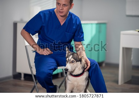 A male vet sitting on a chair posing for a picture with a husky dog.