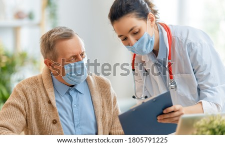 Doctor and senior man wearing facemasks during coronavirus and flu outbreak. Virus and illness protection, home quarantine. COVID-2019 Royalty-Free Stock Photo #1805791225