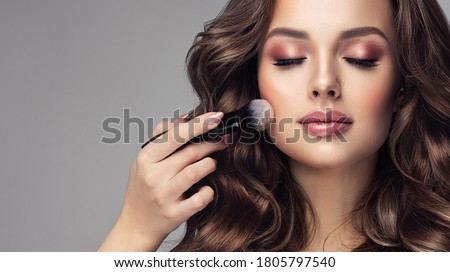 Makeup artist applies   applies powder and blush  . Beautiful woman face. Hand of make-up master puts blush on cheeks  beauty  model girl . Make up in process Royalty-Free Stock Photo #1805797540