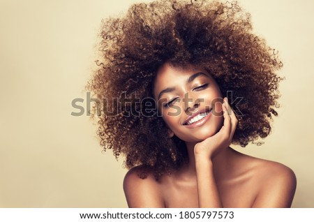 Beauty portrait of african american woman with clean healthy skin on beige background. Smiling beautiful afro girl.Curly black hair #1805797573