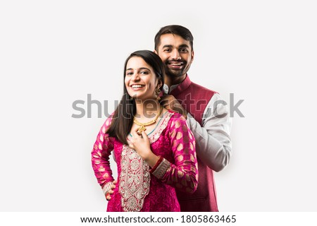 Indian man tying or presenting gold necklace to his beautiful wife on birthday, valentine's day, anniversary or Diwali festival