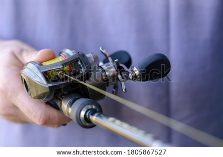 Close-up of male hand with a fishing rod and baitcasting reel. Caucasian man is fishing with casting rod. Sports and recreation. Selective focus. Royalty-Free Stock Photo #1805867527