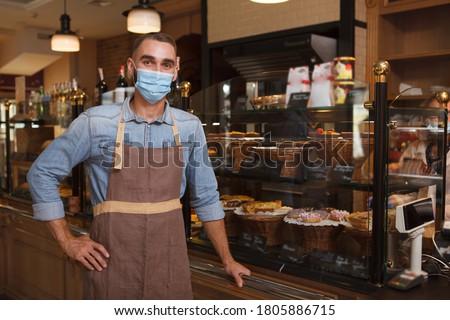 Male baker wearing medical face mask working at his bakery store during coronavirus quarantine Royalty-Free Stock Photo #1805886715