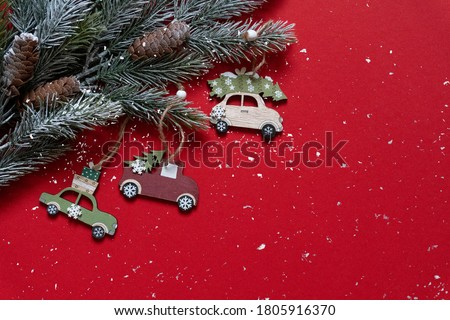 Wooden Christmas and new year toys on Christmas tree branches on the high corner on red background with snow, top view, copy space, banner, holiday mood. #1805916370