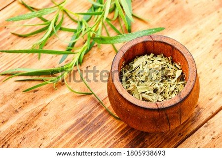 Raw and dry tarragon spice.Tarragon or Artemisia dracunculus on wooden table #1805938693
