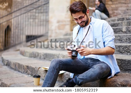 Happy bearded male traveler in casual clothes looking photos on photo camera while resting on stone stairs during summer vacation. Photography courses, studying photographing