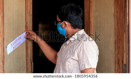 Asian man finds eviction notice on the door of the house Royalty-Free Stock Photo #1805954356