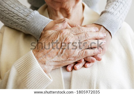 Mature female in elderly care facility gets help from hospital personnel nurse. Senior woman, aged wrinkled skin & hands of her care giver. Grand mother everyday life. Background, copy space, close up Royalty-Free Stock Photo #1805972035