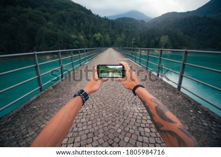 POV shot of man make photo of tourist attraction bridge in mountains on smartphone. Wide angle photo of mobile phone screen. Digital nomad or influencer travel blogger vibes