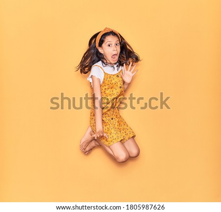 Adorable hispanic child girl scared wearing casual dress and diadem. Jumping over isolated yellow background