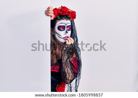 Young woman wearing day of the dead custome holding blank empty banner looking stressed and nervous with hands on mouth biting nails. anxiety problem.