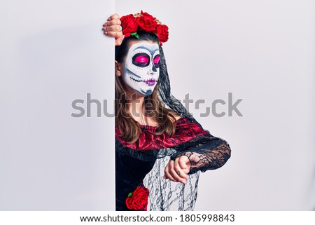 Young woman wearing day of the dead custome holding blank empty banner checking the time on wrist watch, relaxed and confident