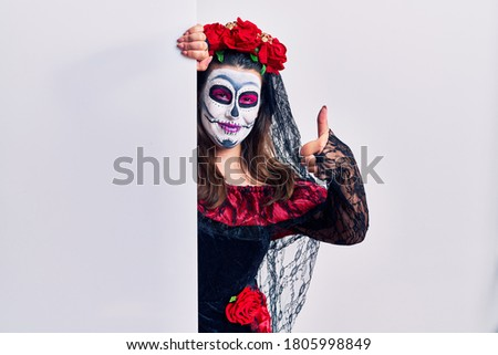 Young woman wearing day of the dead custome holding blank empty banner approving doing positive gesture with hand, thumbs up smiling and happy for success. winner gesture.