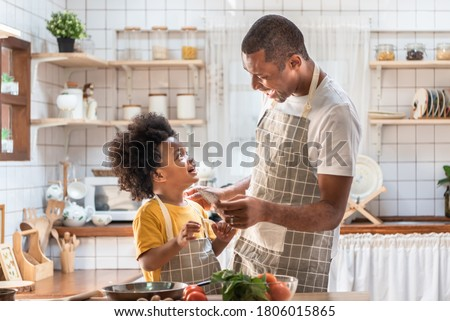 African American Father and little son playing and laughing during cooking in kitchen. Black family having fun preparing healthy food together at home. Brazilian Single dad and boy with smiling face Royalty-Free Stock Photo #1806015865