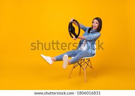 Full body profile photo of pretty funny lady good mood sit chair spread legs playing hold steering wheel riding imagine car wear casual denim shirt shoes isolated yellow color background Royalty-Free Stock Photo #1806016831