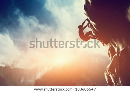 A silhouette of man climbing on rock, mountain at sunset. Adrenaline, strenght, ambition Royalty-Free Stock Photo #180605549