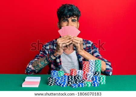 Young hispanic man playing gambling poker covering face with cards smiling with a happy and cool smile on face. showing teeth.