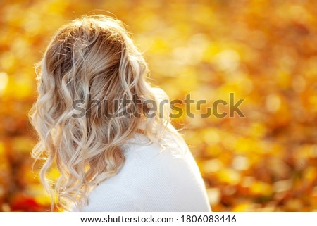 Autumn portrait of  blonde girl outdoors with curly hair. Back view. Copy space