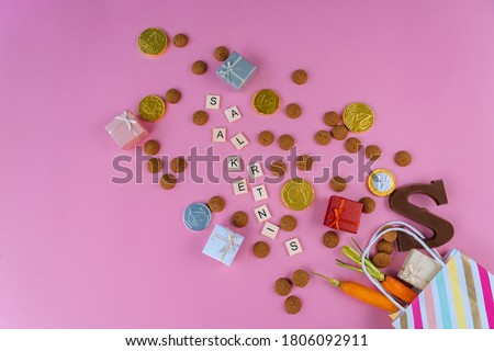 Dutch holiday Sinterklaas Greeting Card. St. Nicholas Day background with traditional food - pepernoten, chocolate letter, gift, carrots for horse. Concept for party in Saint Nicolas day five december Royalty-Free Stock Photo #1806092911