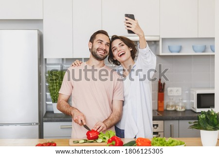 Cheerful young couple friends woman man preparing vegetable salad cooking food in light kitchen at home, doing selfie shot on mobile cell phone gadget. Dieting family healthy lifestyle concept.