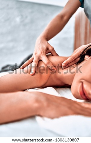 Masseur doing massage on woman body in the spa salon. Beauty treatment concept. Vertical photo