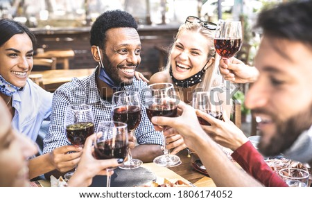 Friends toasting red wine at outdoor restaurant bar with open face mask - New normal lifestyle concept with happy people having fun together on warm filter - Focus on afroamerican guy Royalty-Free Stock Photo #1806174052