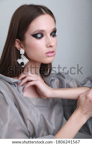 Stylish young model in silver transparent blouse and black and white handmade earrings, posing at the white wall background touching her neck. Fashionable image for magazine with free space copyright