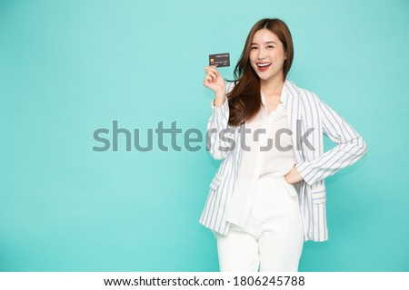 Young beautiful Asian woman smiling, showing, presenting credit card for making payment or paying online business, Pay a merchant or as a cash advance for goods, Cardholder or A person who owns a card #1806245788