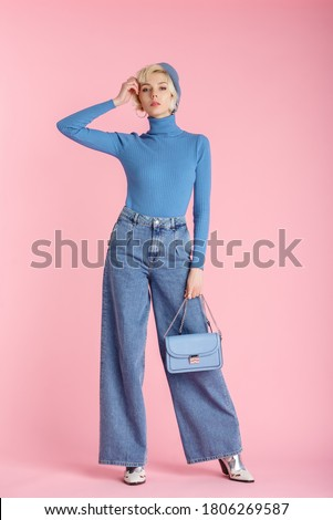 Full body fashion portrait of young elegant model wearing trendy wide leg jeans, light blue turtleneck, beret, holding small bag, posing on pastel pink background  Royalty-Free Stock Photo #1806269587