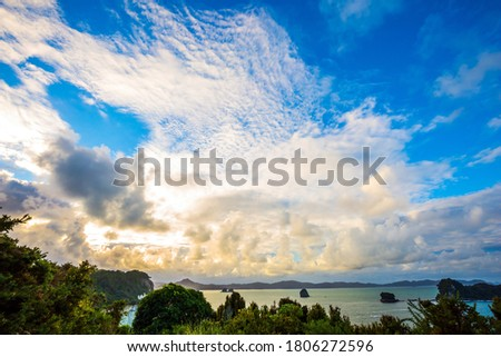 Cathedral Cove on Coromandel Peninsula on the North Island. New Zealand. Lush clouds of strange shapes. Journey to the edge of the Earth.  The concept of active, exotic, ecological and photo tourism