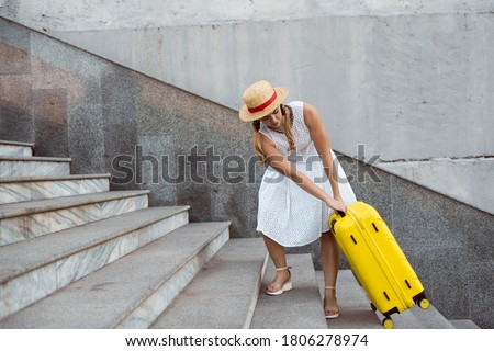 Beautiful tourist girl travels. Pulls a large yellow suitcase up the steps. Heavy load. Royalty-Free Stock Photo #1806278974