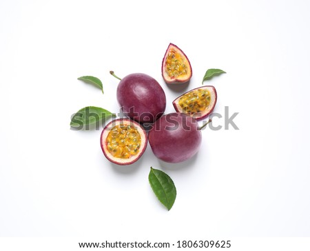 Fresh ripe passion fruits (maracuyas) with leaves on white background, flat lay Royalty-Free Stock Photo #1806309625