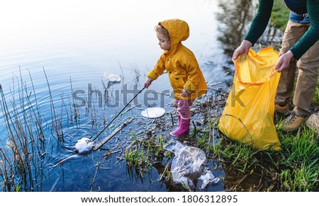 Father with small daughter collecting rubbish outdoors in nature, plogging concept. Royalty-Free Stock Photo #1806312895