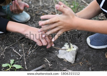 Child boy makes fire by friction method. Survival skills in the forest. Children's tourist rest in the wild. Child hiker in the forest alone.