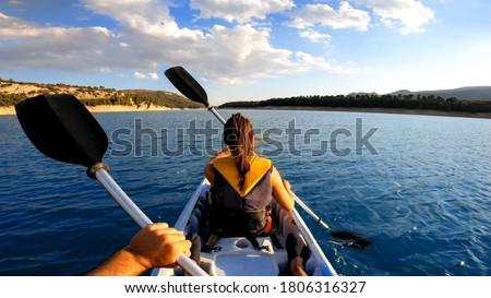 Kayakers rowing at lake. Pov of woman kayaking in beautiful landscape at Embalse de la Bolera, Spain. Aquatic sports in kayak during summer concept. Royalty-Free Stock Photo #1806316327
