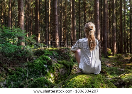 Woman sitting in green forest enjoys the silence and beauty of nature. Royalty-Free Stock Photo #1806334207
