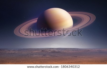 Landscape with saturn planet in sky with stars. Fantasy space wallpaper with planet over the land. Sci-fi. Elements of this image furnished by NASA Royalty-Free Stock Photo #1806340312
