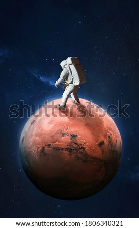 Astronaut on surface of red planet Mars. Martian colonizer. Spaceman. Expedition to Mars. Elements of this image furnished by NASA. Royalty-Free Stock Photo #1806340321